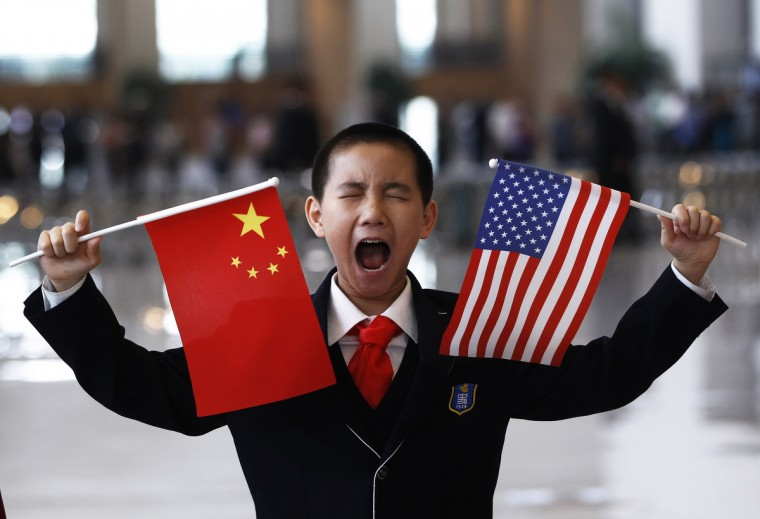A boy who is waiting to greet U.S. Secretary of State Hillary Clinton at the National Museum makes a face while holding the U.S. and Chinese flags in Beijing May 4, 2012. (Shannon Stapleton/Reuters)