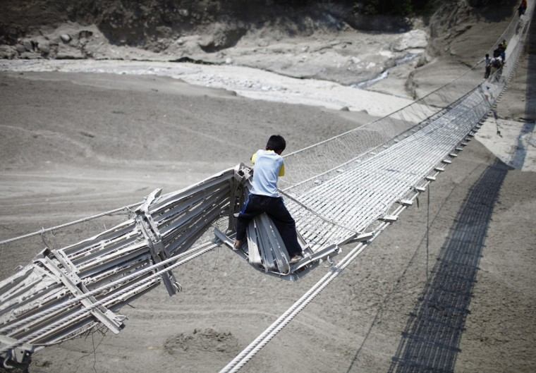 A boy tries to cross a damaged suspension bridge, after a flash flood caused by an avalanche in the Annapurna mountain range on Saturday, in Kaski district May 6, 2012. At least 17 people, including three foreigners, are confirmed to have died during the flood in Pokhara and adjoining villages in Kaski district, according to Police inspector Ravindra Nath Poudel of Kaski District. (Navesh Chitrakar/Reuters)