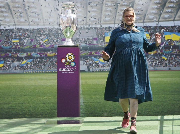 A woman poses for pictures next to the Euro 2012 trophy during a display to the public in central Kiev May 12, 2012. Kiev is set to host the final match of the Euro 2012 soccer tournament. (Gleb Garanich/Reuters)