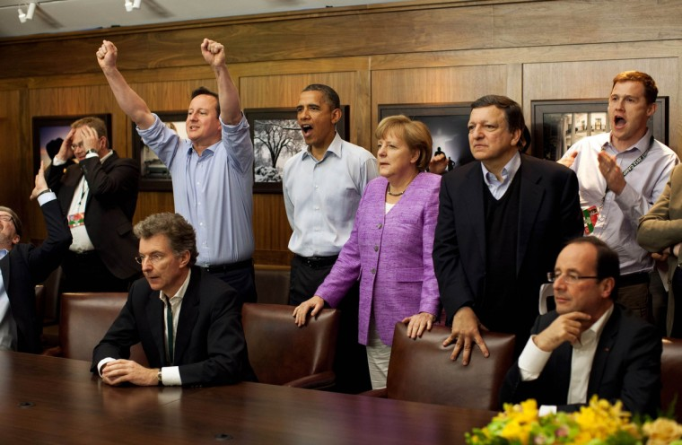 Prime Minister David Cameron of Britain (centre L-R) , President Barack Obama, Chancellor Angela Merkel of Germany, Jose Manuel Barroso, President of the European Commission, and others watch the overtime shootout of the Chelsea vs. Bayern Munich Champions League final in the Laurel Cabin conference room during the G8 Summit at Camp David, Maryland, May 19, 2012. (Pete Souza/White House/Reuters)