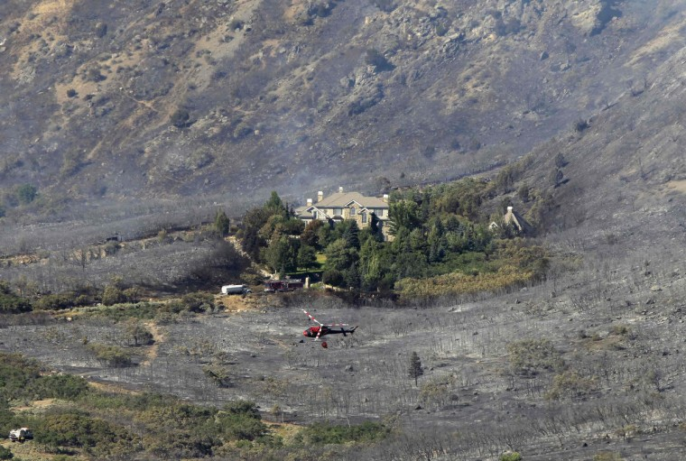 A house is surrounded by a burnt landscape, as a helicopter flies above after dropping water on the Quail Fire in Alpine, Utah, July 3, 2012. The fire started on Tuesday afternoon and spread quickly through the eastern end of Alpine and then up the mountain side. It is still out of control. (George Frey/Reuters)