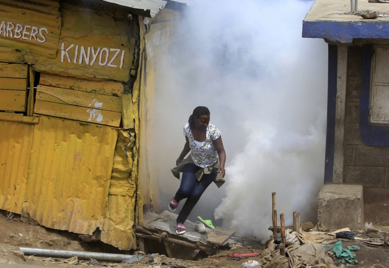 A woman escapes from a cloud of tear gas thrown by the police during the second day of skirmishes in the Eastleigh neighborhood of Kenya's capital Nairobi, November 19, 2012. Police fired tear gas to disperse Kenyans who threw stones and broke into the homes and shops of ethnic Somalis in Nairobi's Somali-dominated Eastleigh neighborhood on Monday to protest against a bomb attack in the district on Sunday. (Noor Khamis/Reuters)