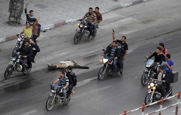 "Palestinian gunmen ride motorcycles as they drag the body of a man, who was suspected of working for Israel, in Gaza City November 20, 2012. Palestinian gunmen shot dead six alleged collaborators in the Gaza Strip who ""were caught red-handed"", according to a security source quoted by the Hamas Aqsa radio on Tuesday. (Suhaib Salem/Reuters)"