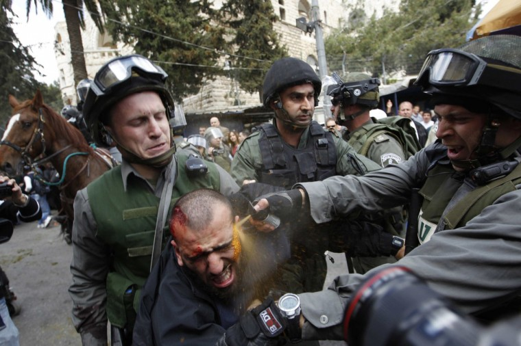 Israeli border police officers use pepper spray as they detain an injured Palestinian protester during clashes on Land Day after Friday prayers outside Damascus Gate in Jerusalem's Old City March 30, 2012. Israeli security forces fired rubber bullets, tear gas and stun grenades to break up groups of Palestinian stone-throwers on Friday as annual Land Day rallies turned violent. Police said they had made five arrests at Damascus Gate. Land Day commemorates the killing by security forces of six Arabs in 1976 during protests against government plans to confiscate land in northern Israel's Galilee region. (Ammar Awad/Reuters)