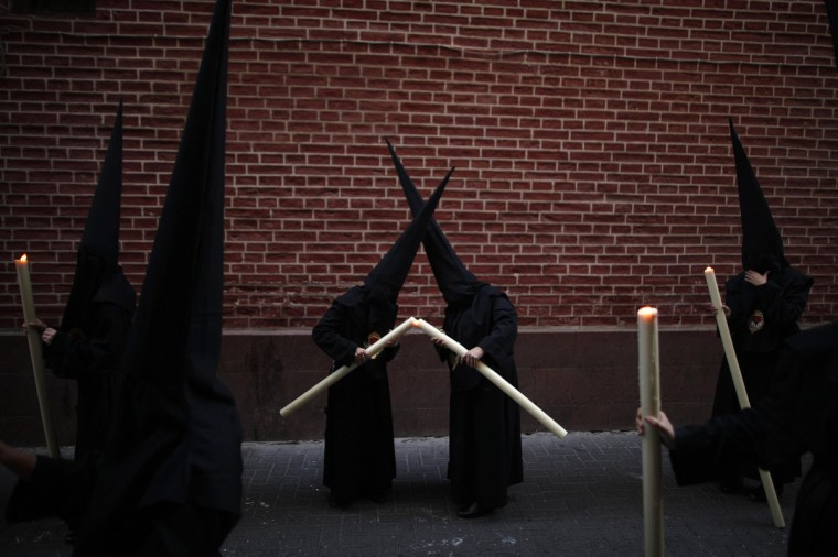 Penitents light their candles as they take part in the Calvario brotherhood procession during Holy Week in Malaga, southern Spain, April 6, 2012. Hundreds of processions take place around the clock in Spain during Holy Week, drawing thousands of visitors. Picture taken April 6, 2012. (Jon Nazca/Reuters)