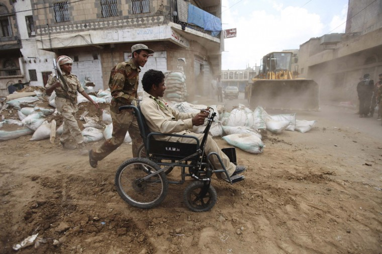 A defected army soldier pushes a disabled person across a street as barricades erected by defected army forces are dismantled in Sanaa April 7, 2012. (Mohamed al-Sayaghi/Reuters)