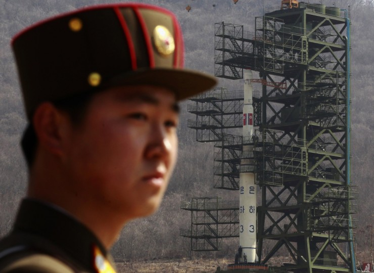 A soldier stands guard in front of the Unha-3 (Milky Way 3) rocket sitting on a launch pad at the West Sea Satellite Launch Site, during a guided media tour by North Korean authorities in the northwest of Pyongyang April 8, 2012. (Bobby Yip/Reuters)