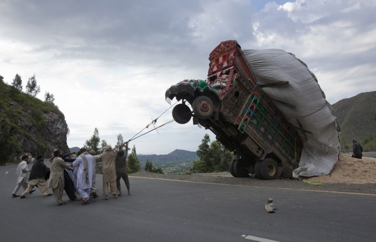 Men use ropes to try and right a supply truck overloaded with wheat straw, used as animal feed, along a road in Dargai, in the Malakand district, about 165 km (100 miles) northwest of Pakistan's capital Islamabad, April 13, 2012. (Mian Khursheed/Reuters)