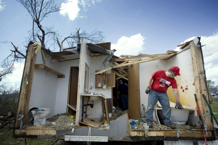 Tim Crom picks up debris from a damaged home in Thurman, Iowa April 15, 2012. Rescue and clean-up efforts were underway across the Midwest on Sunday after dozens of tornados tore through the region, killing at least five people in Oklahoma, leaving thousands without power in Kansas and damaging up to 90 percent of the homes and buildings in one small Iowa town. (Lane Hickenbottom/Reuters)