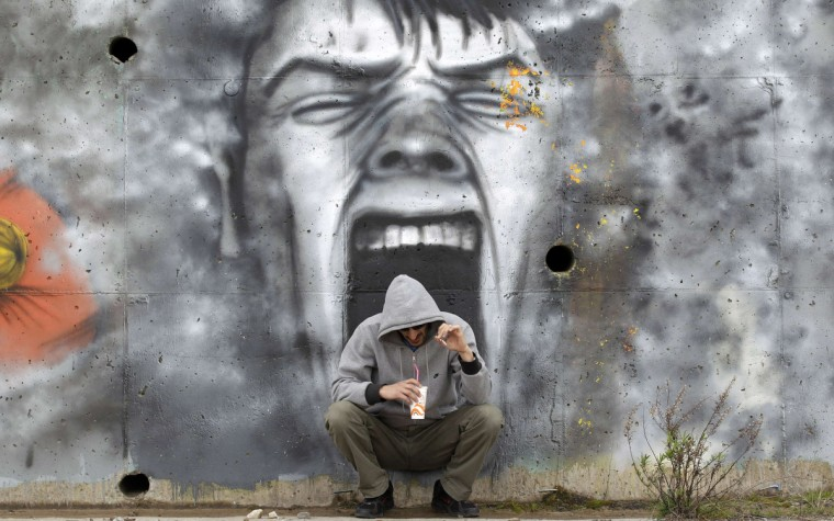 A man drinks coffee in front of a mural near the coastal town of Kalamatta in the Messinia area of Greece March 23, 2012. (Cathal McNaughton/Reuters)