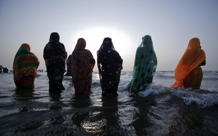 "Hindu devotees pray while standing in the waters of the Arabian Sea as they worship the Sun god during the Hindu religious festival ""Chhat Puja"" in Mumbai, November 19, 2012. Hindu devotees worship the Sun god and fast all day for the betterment of their family and society during the festival. (Vivek Prakash/Reuters)"
