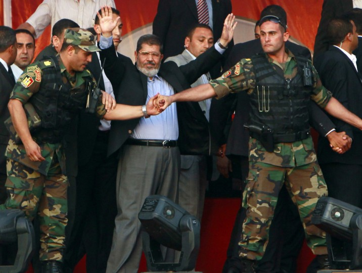 Egypt's Islamist President-elect Mohamed Mursi waves to his supporters while surrounded by his members of the presidential guard in Cairo's Tahrir Square, June 29, 2012. Mursi took an informal oath of office on Friday before tens of thousands of supporters in Cairo's Tahrir Square, in a slap at the generals trying to limit his power. (Amr Abdallah Dalsh/Reuters)