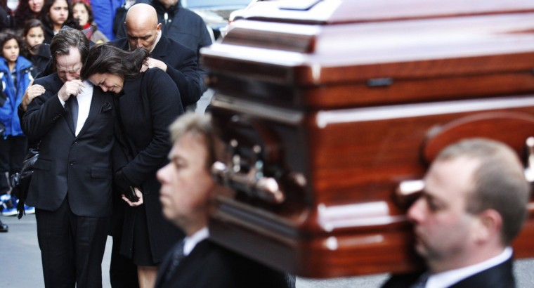 Madonna and Matthew Badger (L) cry as one of their daughters' casket arrives for their funeral service at Saint Thomas Church in New York January 5, 2012. A raging Christmas-morning house fire that killed Madonna Badger's elderly parents and her three young daughters, Lily, Grace, and Sarah, in Stamford, Connecticut, appears to have been caused by embers from a fireplace and was accidental, city officials said on Tuesday. (Eduardo Munoz/Reuters)