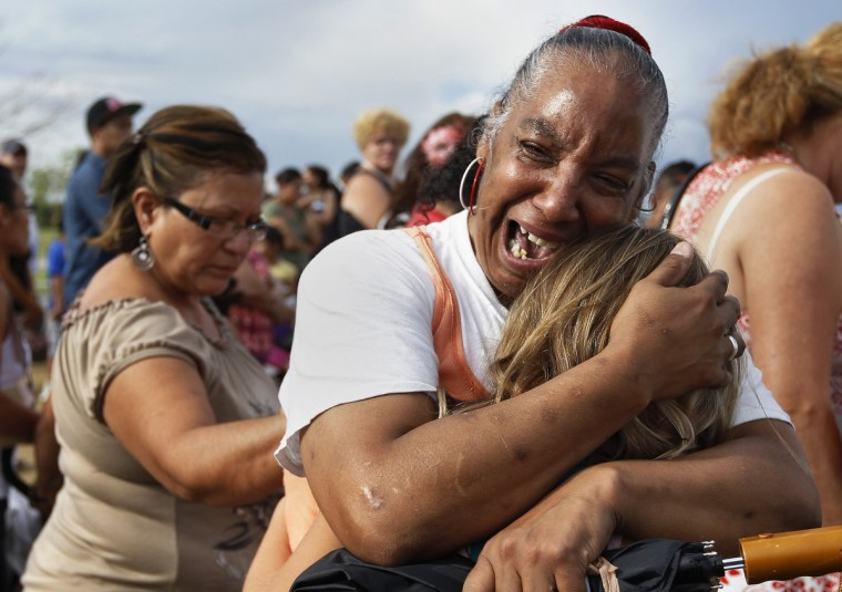 """Denise Paba, who lost her 6-year-old niece Veronica Moser, cries during a memorial for victims behind the theatre where a gunman opened fire last Friday on moviegoers in Aurora, Colorado July 22, 2012. Residents of a Denver suburb mourned their dead on Sunday from a shooting rampage by a """"demonic"""" gunman who killed 12 people and wounded 58 after opening fire at a cinema showing the new Batman movie. President Barack Obama headed to Aurora, on Sunday to meet families grieving their losses Friday's mass shooting that has stunned the nation and rekindled debate about guns and violence in America. (Shannon Stapleton/Reuters)"""