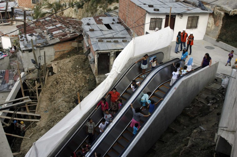 People travel on an outdoor public escalator at Commune 13 in Medellin January 12, 2012. A huge 384 metres (1,260 ft) long outdoor escalator, divided into six sections, has been erected in one of the poorest districts of Colombia's second largest city to help the 12,000 residents there get around. (Fredy Builes/Reuters)
