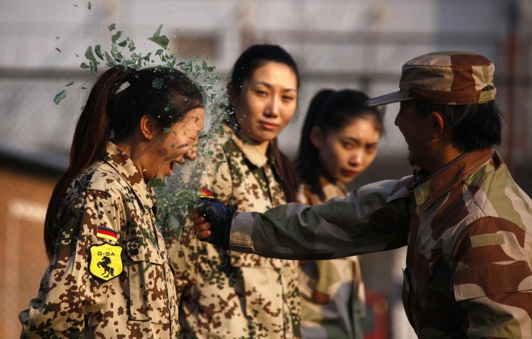 An instructor from the Tianjiao Special Guard/Security Consultant Ltd. Co, smashes a bottle over a female recruit's head during a training session for China's first female bodyguards in Beijing January 13, 2012. According to the company, the training session consists of 20 women, mostly college graduates, who will undergo 8-10 months of training to develop sufficient skills to become security guards. The company will then offer the best trainee a chance to attend the International Security Academy in Israel. (David Gray/Reuters)