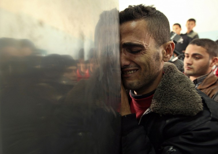 A Palestinian man reacts upon the arrival of the body of a man, killed by an Israeli strike, at a hospital in Beit Hanoun in the northern Gaza Strip January 18, 2012. An Israeli aircraft and tank strike killed at least one Palestinian close to the border fence in the Hamas-controlled Gaza Strip on Wednesday, medics said. (Mohammed Salem/Reuters)