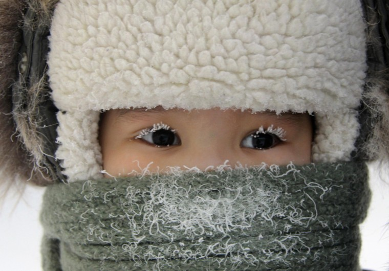 A child, with eyelashes covered with hoarfrost, is seen along a street in the eastern Siberian city of Yakutsk in Sakha (Yakutia) Republic February 10, 2012. The air temperature in Yakutsk is about minus 35 degrees Celsius (minus 31 degrees Fahrenheit). (Viktor Everstov/Reuters)