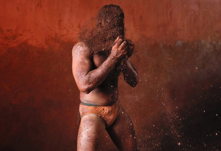 A wrestler rubs his hands with mud to prevent slipping due to sweat, during a traditional mud wrestling (Kushti) bout at the Akhaara centre in Kolhapur, about 400 kms (250 miles) south of Mumbai, February 14, 2012. Fewer people are taking up Kushti, according to the sport's coaches, as young athletes turn instead to mat wrestling to gain access to top international sports competitions. (Danish Siddiqui/Reuters)
