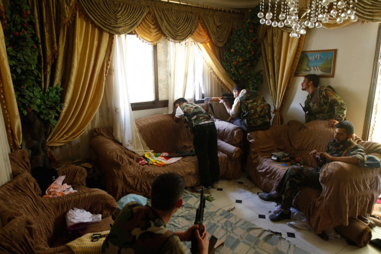 A Free Syrian Army fighter fires his sniper rifle from a house in Aleppo August 14, 2012. (Goran Tomasevic/Reuters)