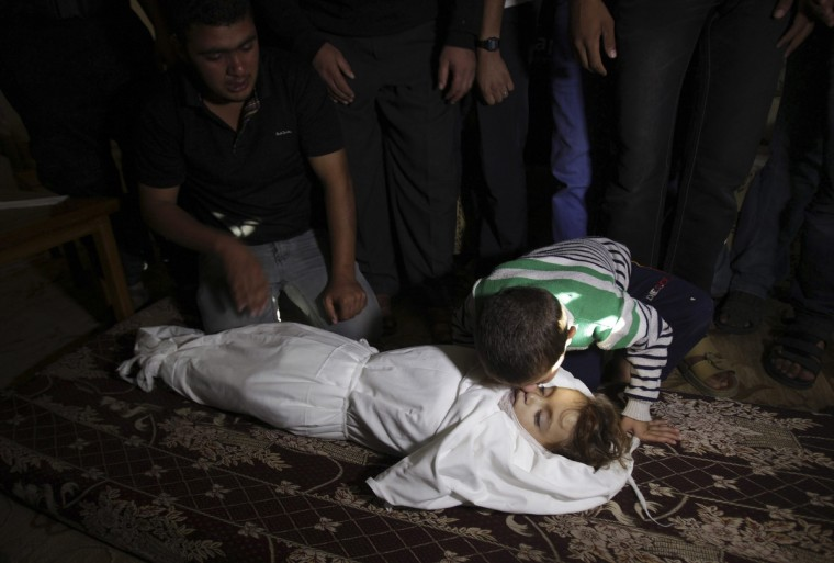 The brother of Palestinian boy Walid al-Abadlah, who according to hospital officials was killed in an Israeli air strike, kisses his body during his funeral in Khan Younis in the southern Gaza Strip November 15, 2012. A Hamas rocket killed three Israelis north of the Gaza Strip on Thursday, drawing the first blood from Israel as the Palestinian death toll rose to 15 including Walid al-Abadlah in a military showdown lurching closer to all-out war and an invasion of the enclave. (Ibraheem Abu Mustafa/Reuters)