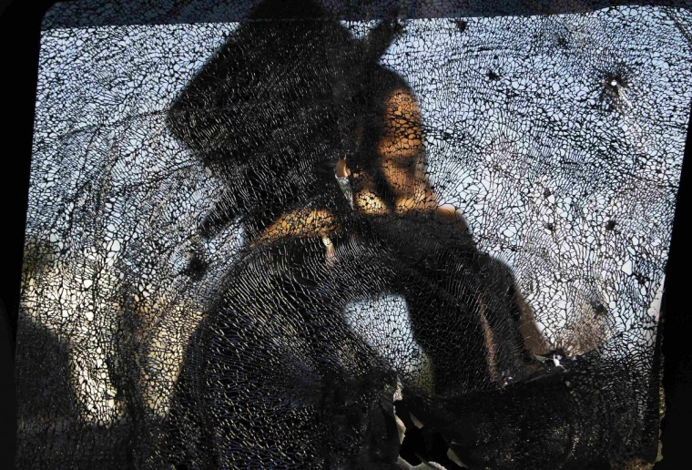 An ultra-Orthodox Jewish man is seen through a damaged car window after a rocket fired from Gaza landed in the southern city of Ashdod November 16, 2012. Israel has started drafting 16,000 reserve troops, the military said on Friday, in a sign that violence could escalate further with Palestinian militants in the Gaza Strip. (Amir Cohen/Reuters)