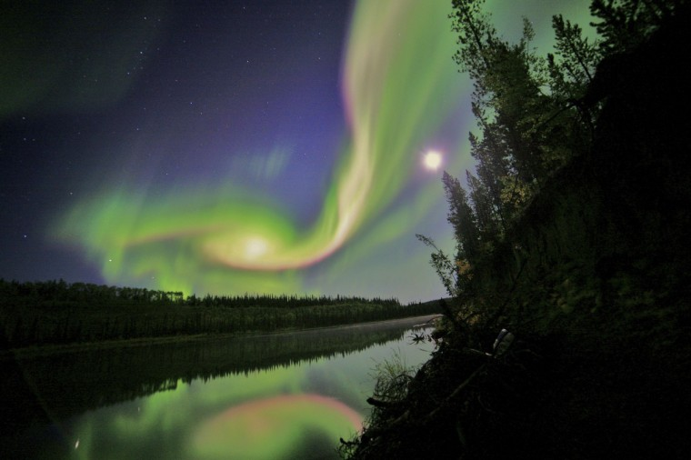 Swirls of green and red appear in an aurora over Whitehorse, Yukon on the night of September 3, 2012 in this NASA handout image. The aurora was due to the interaction of a coronal mass ejection (CME) from the sun with Earth's magnetosphere. The CME left the Sun on August 31 and arrived on September 3. (David Cartier, Sr./NASA via Reuters)