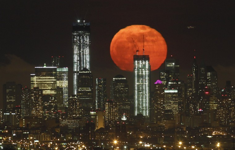 A full moon as seen from West Orange, New Jersey, rises over the skyline of Lower Manhattan and One World Trade Center (L) in New York, May 6, 2012. (Gary Hershorn/Reuters)