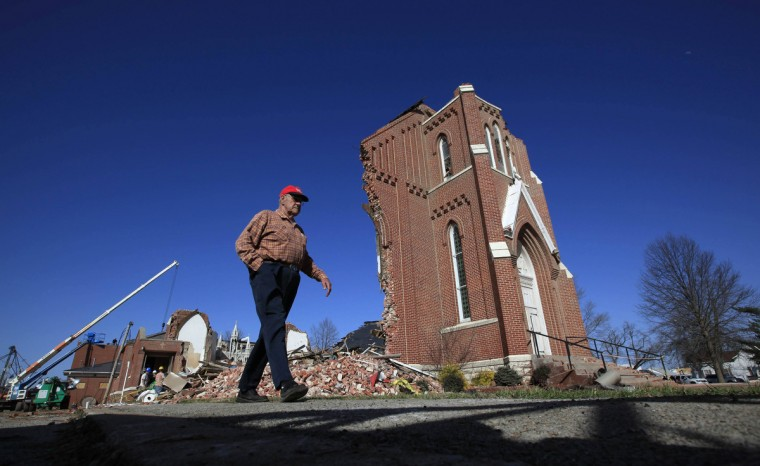A man walks by the destroyed St. Joseph's Catholic Church which was damaged by a tornado in Ridgway, Illinois, March 1, 2012. Powerful storms that spawned tornadoes ripped through the U.S. Midwest on Wednesday, killing at least 12 people, including six in Illinois who were crushed when a house was lifted up and fell on them, authorities said. (Jim Young/Reuters)