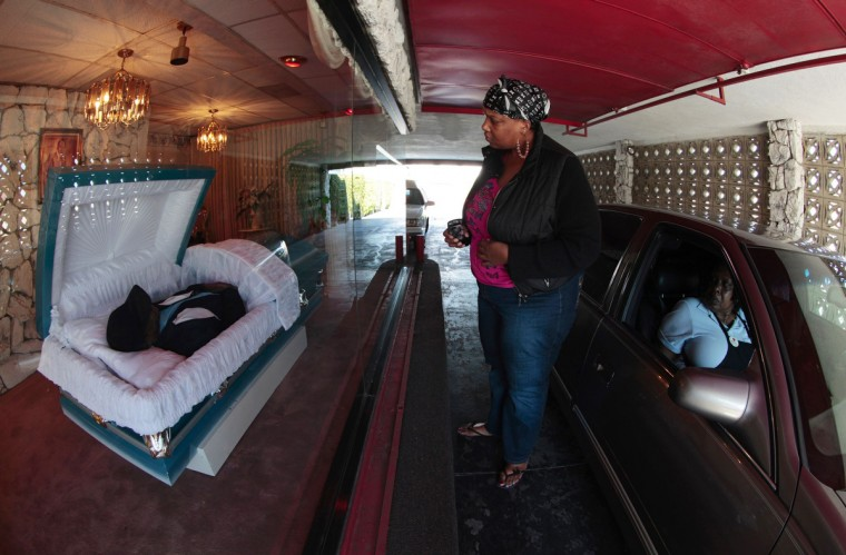 Flo Watson, 61, (R) and her daughter Nina Watson, 34, (C) view Flo's late postal service co-worker Robert Sanders, 58, at the Robert L. Adams drive-through funeral parlor in Compton, Los Angeles, February 8, 2012. The funeral parlor has been in business since 1974, and is thought to be the only drive-through funeral home in southern California, according to office manager Denise Knowles-Bragg. Knowles-Bragg said the parlor offers a convenient alternative to older people who find it hard to walk, those who want to make a quick stop during the lunch hour, and the families of well-known deceased people who expect many visitors. (Lucy Nicholson/Reuters)