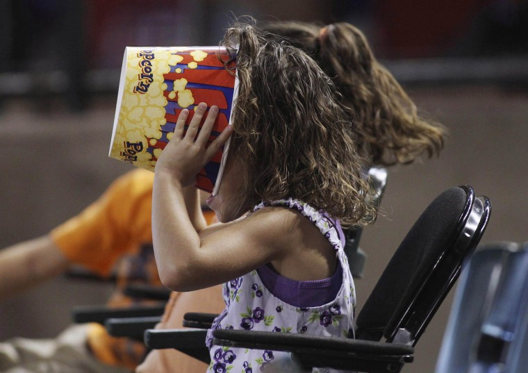 A young baseball fan makes sure there's not a kernel of popcorn left as she watches the Chicago Cubs play the Arizona Diamondbacks during their MLB National League baseball game in Phoenix, Arizona, June 24, 2012. (Darryl Webb/Reuters)