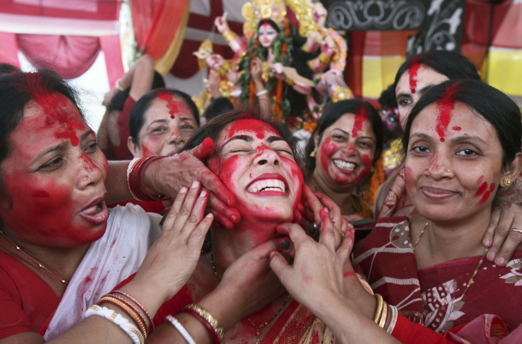 """A Hindu woman reacts as she is smeared with """"sindhur"""", or vermillion powder, as part of a ritual on the last day of the Durga Puja festival in the northern Indian city of Chandigarh October 24, 2012. In Hindu mythology, Durga symbolises power and the triumph of good over evil. The Durga Puja is the biggest religious festival of Bengali Hindus. (Ajay Verma/Reuters)"""