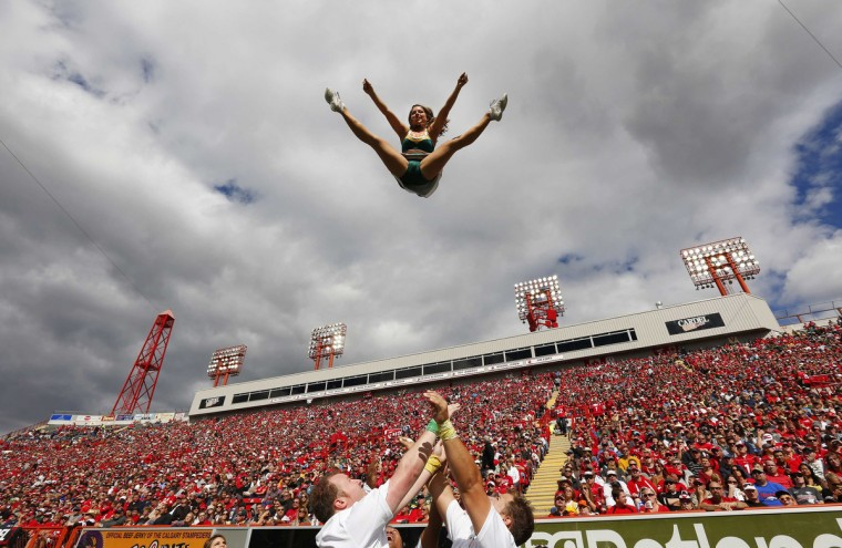 A member of the Edmonton Eskimos cheer squad flies through the air during the first half of their CFL football game against the Calgary Stampeders in Calgary, Alberta September 3, 2012. (Todd Korol/Reuters)