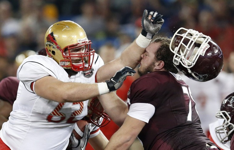 Laval Rouge et Or Philippe Gagnon (L) knocks the helmet from the head of McMaster Marauders Adam Dickson during the Vanier Cup University Championship football game in Toronto, November 23, 2012. (Mark Blinch/Reuters)