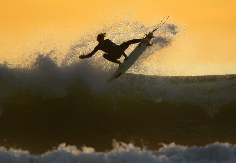 A young surfer sails his board off a wave as large swells hit the California coastline at dusk in Cardiff, California, January 5, 2012. (Mike Blake/Reuters)