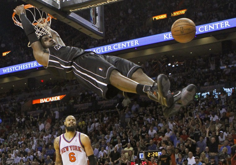 Miami Heat's LeBron James hangs on the rim after his dunk near New York Knicks Tyson Chandler during their NBA basketball game in Miami, Florida February 23, 2012. (Andrew Innerarity/Reuters)
