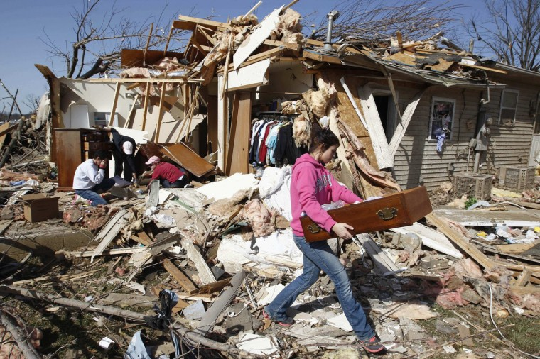 Jordan Youssef salvages a dresser drawer from the remains of her grandmother's house which was destroyed by a tornado in Harrisburg, Illinois March 1, 2012. Powerful storms that spawned tornadoes ripped through the U.S. Midwest on Wednesday, killing at least 12 people, including six in Illinois who were crushed when a house was lifted up and fell on them, authorities said. (Jim Young/Reuters)