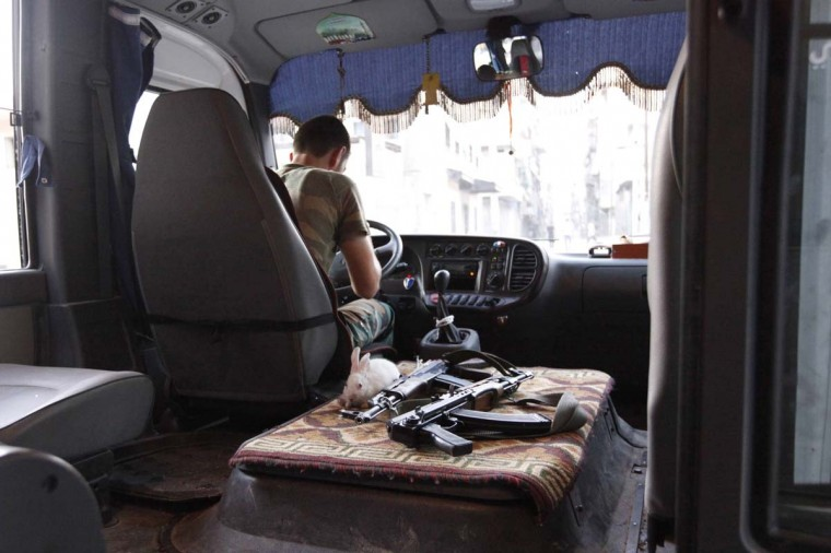 A rabbit is pictured next to weapons in a Free Syrian Army bus in Bustan Al-Basha district in Aleppo September 18, 2012. (Zain Karam/Reuters)