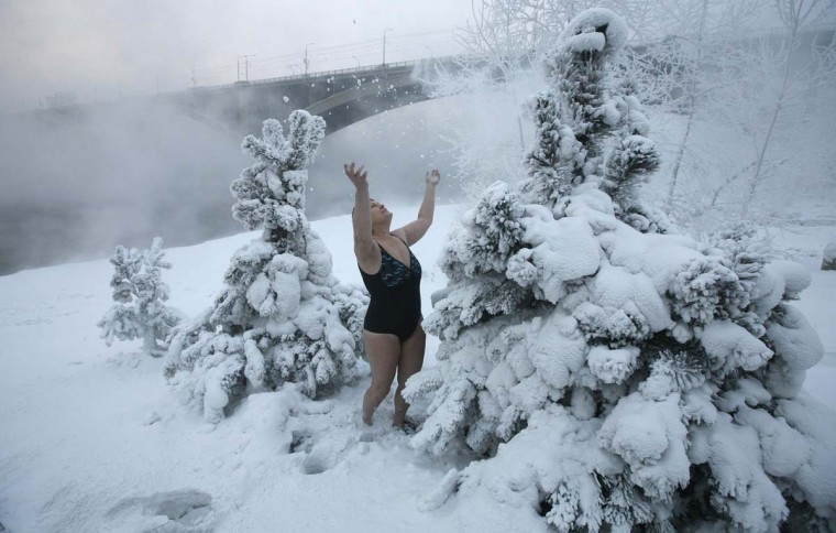 "Lyubov Valiyeva, a member of the ""Cryophil"" winter swimming club, plays with the snow by the bank of the Yenisei River with the air temperature at minus 13 degrees Fahrenheit in the Siberian city of Krasnoyarsk, December 26, 2012. (IIya Naymushin/Reuters)"
