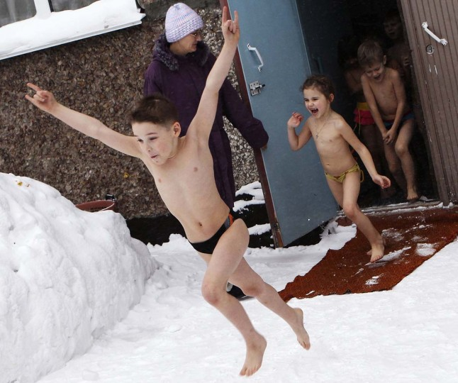 Children run out into the yard to pour cold water on themselves during daily exercises at a kindergarten, in air temperatures of minus 13 degrees Fahrenheit in Barnaul, the capital of the Altai region, December 26, 2012. (Andrei Kasprishin/Reuters)
