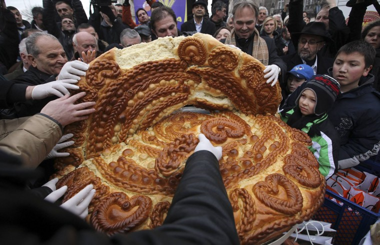 People gather to receive a piece of traditional Christmas bread, marking the Orthodox Christmas Day festivities, at Terazije Square in Belgrade on January 7, 2011. Serbian Orthodox believers celebrate Christmas on January 7, which is December 25th on the Julian calendar. (Marko Djurica/Reuters)