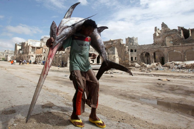 A fisherman carries a swordfish on his back from the Indian Ocean waters to the market in Somalia's capital Mogadishu. (Ismail Taxta /Reuters)