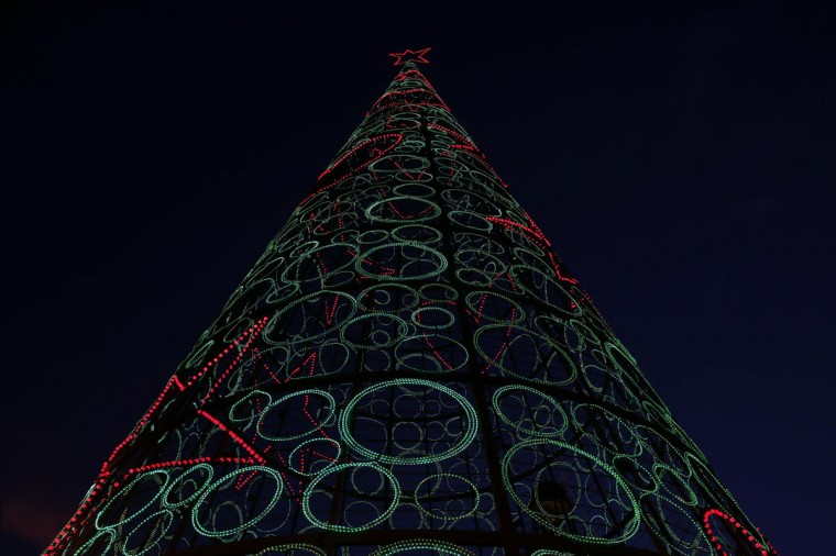 A Christmas tree made out of lights is illuminated at Madrid's landmark Puerta del Sol square on December 12. (Juan Medina/Reuters)