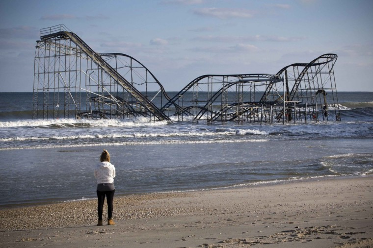 A woman looks at a roller coaster sitting in the ocean, when the boardwalk it was built upon collapsed during Hurricane Sandy, in Seaside Heights, New Jersey November 28, 2012. The storm made landfall along the New Jersey coastline on October 29, 2012. (Andrew Burton/Reuters)