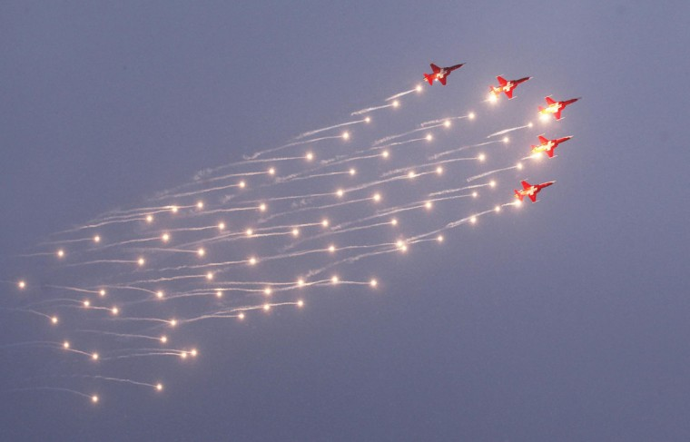 Patrouille Suisse Northrop F-5E Tiger II jet release flares during a flight demonstration at a Swiss Air Force commando handover ceremony at the Swiss Army Airbase in Duebendorf near Zurich, Switzerland. (Michael Buholzer/Reuters)