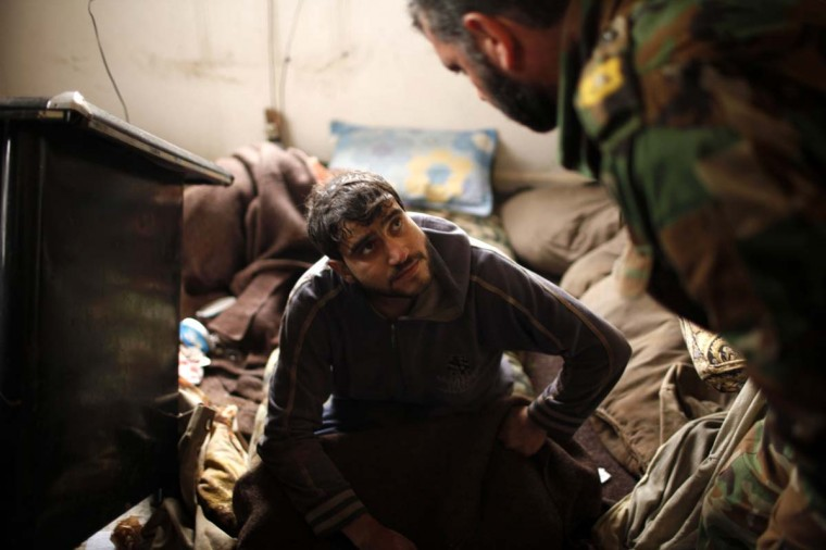 A detainee Syrian soldier loyal to Syria's President Bashar al-Assad is questioned by a Free Syrian Army officer at the army base at Hawa village, north Aleppo December 23, 2012. The Free Syrian Army fighters controlled the Syrian Army base at Hawa Village yesterday.(Ahmed Jadallah/Reuters)
