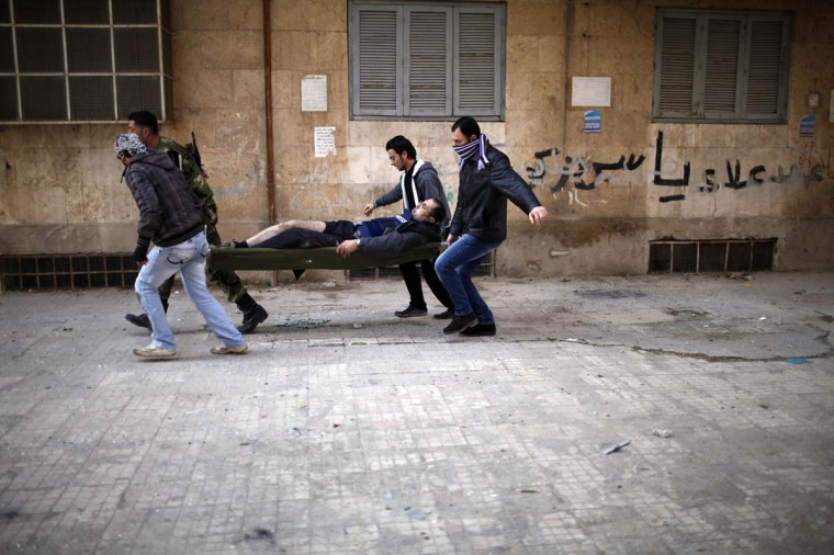 Ayman al-Sahili, a Reuters cameraman who was shot in the leg while filming on the front line by a sniper loyal to Syrian President Bashar el-Assad is carried away in Syria's north city of Aleppo December, 31, 2012. (Ahmed Jadallah/Reuters)