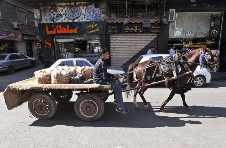 A street vendor rides a horse-cart as he sells potatoes on a street in Damascus November 13, 2012. (Muzaffar Salman/Reuters)