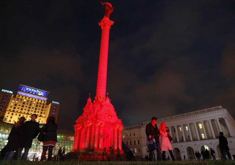 Visitors walk around the Monument of Independence, lit in red to mark World AIDS Day, on Independence Square in Kiev, Ukraine. (Anatolii Stepanov/Reuters)