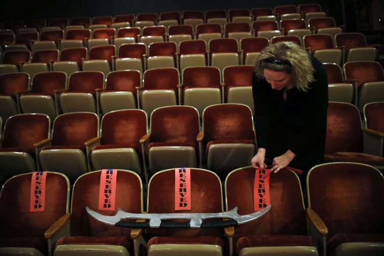 "A woman lays out markers on seats beside a weapon called a ""bat'leth"" before a performance of ""A Klingon Christmas Carol"" in Chicago, December 20, 2012. (Jim Young/Reuters)"